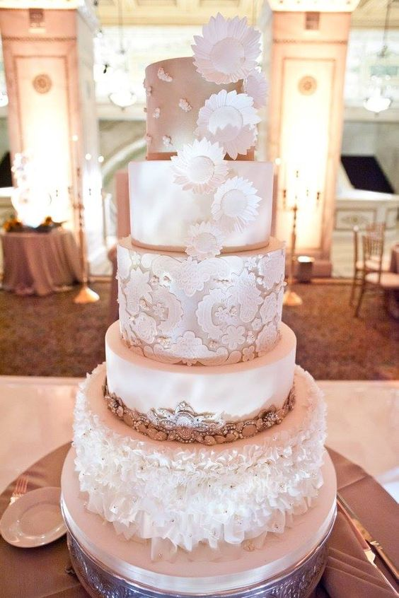 a refined five tier wedding cake with all mismatched tiers, lace, embellishments, ruffles, sugar blooms and much other detailing