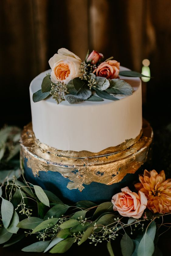 a refined navy and white two-tier wedding cake with gold decor, foliage and pastel blooms is a very chic idea