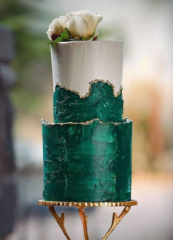 a refined two-tier wedding cake in emerald and white, with a gold edge, neutral blooms on top is pure luxury