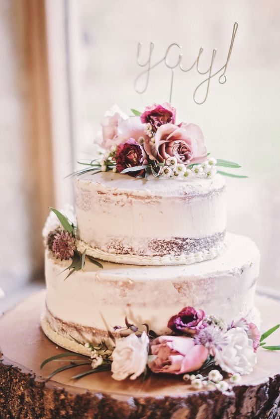 a rustic two-tier naked wedding cake with pastel and burgundy blooms and a calligraphy topper is a pretty idea