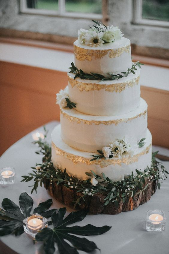 a semi-naked four tier wedding cake with gold leaf, greenery and white blooms is a very chic and refined idea