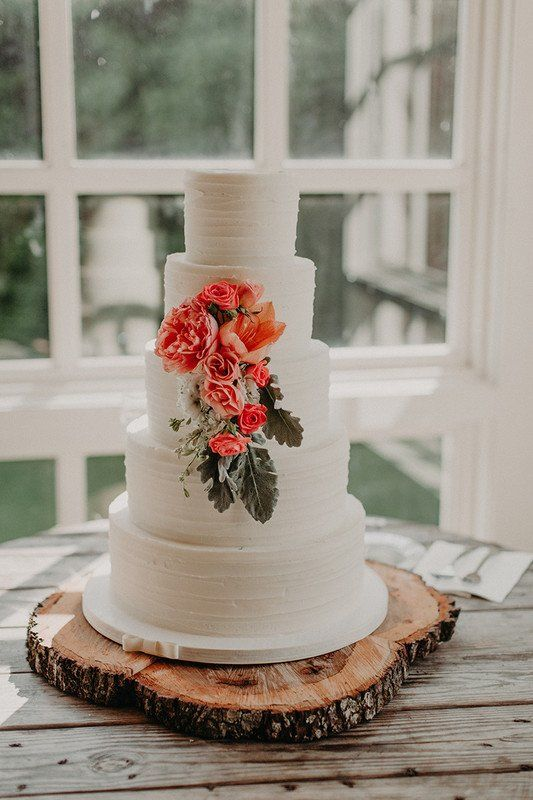 a simple and cool white textural buttercream wedding cake with bold peachy blooms and greenery is a wow idea