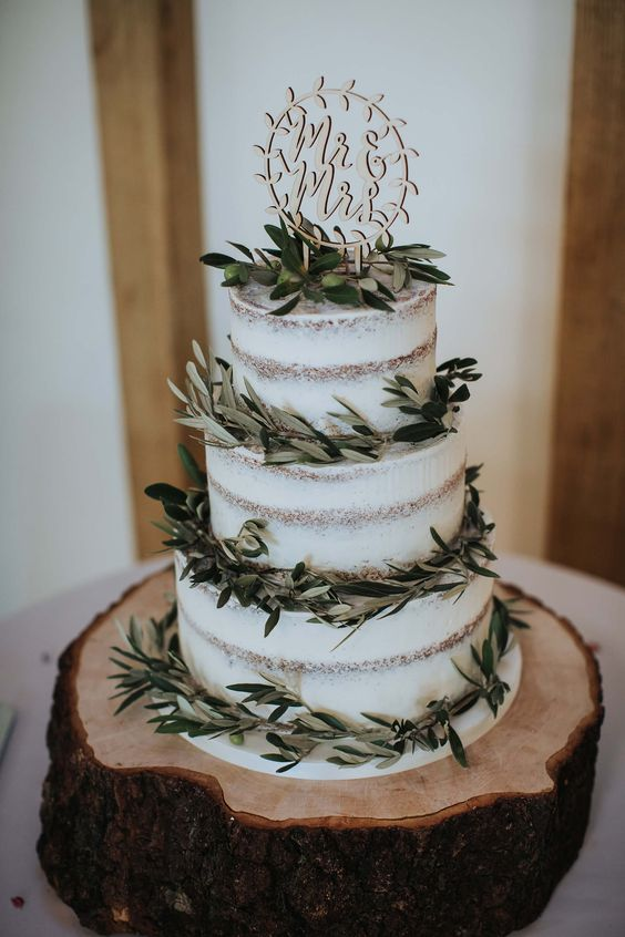 a simple naked three-tier wedding cake with fresh greenery and olives and a fun carved topper is a lovely idea