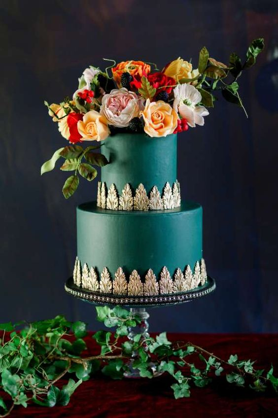 a sophisticated emerald two-tier wedding cake with gold leace decor, bold blooms, greenery and blackberries on top