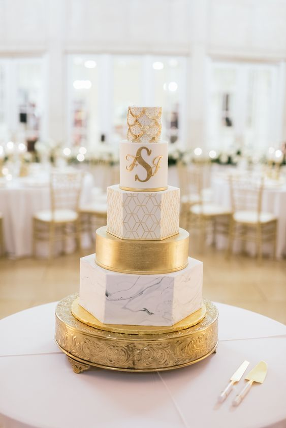 a sophisticated gold and white five tier wedding cake with all mismatched tiers - patterned, textural, marble and gold ones