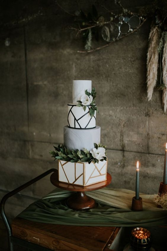 a stylish four tier wedding cake with marble and geometric tiers, greenery and white blooms is a trendy and chic idea
