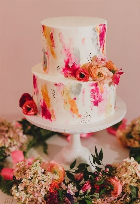 a super bright two-tier wedding cake with bold watercolors, speckles and bright blooms is a great idea for a summer wedding