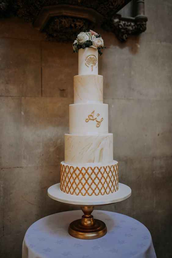 a tall refined five tier wedding cake with marble, patterned and leaf tiers plus fresh neutral blooms on top is wow
