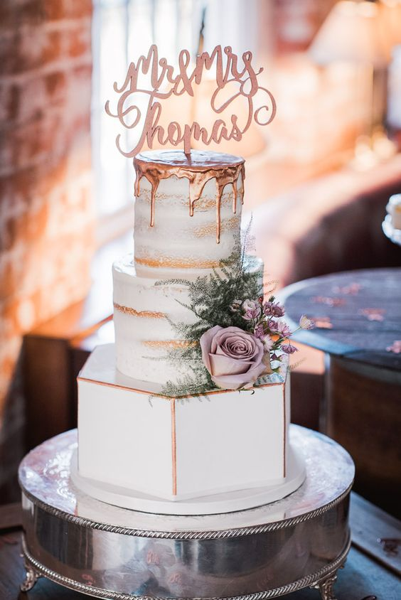 a three-tier wedding cake with two naked tiers and a sleek buttercream one, with copper drip and blooms and greenery