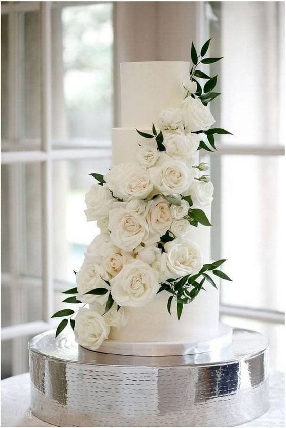 a traditionally elegant four tier plain white wedding cake with white roses and greenery is a very refined and chic idea