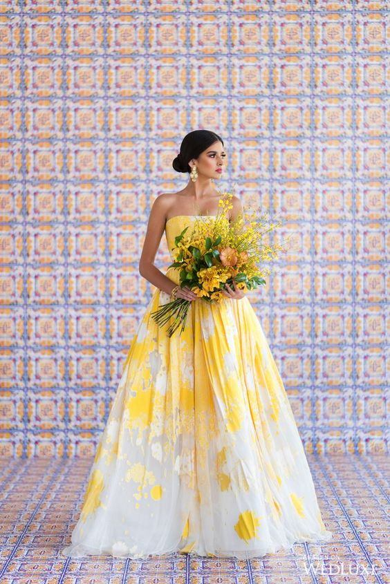 a unique and bold strapless wedding ballgown in yellow and white, with a chaotic pattern, statement earrings for a stunning look
