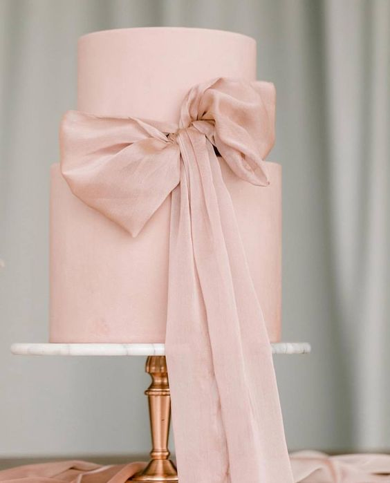 a very chic and girlish wedding cake in pink, with no detailing except for a large ribbon bow is pure perfection