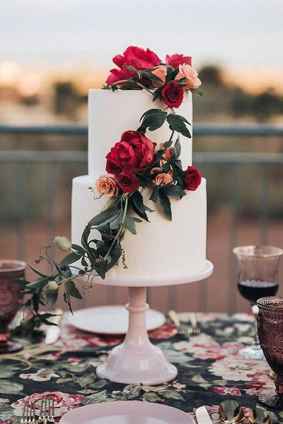 a very elegant two-tier wedding cake, a white and sleek one, with bold blooms and greenery going down is pure chic