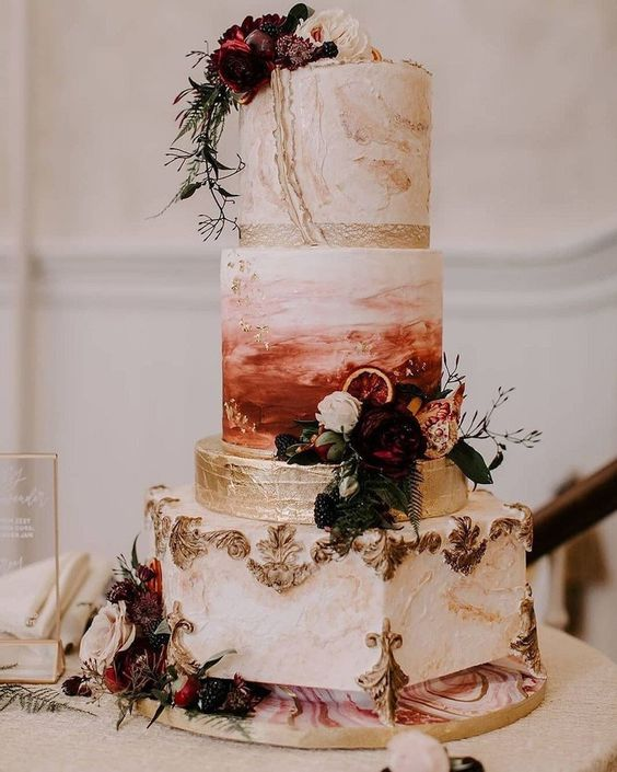 a whimsical and refined four tier wedding cake with mismatching tiers with gold patterns, gold leaf, an ombre effect and bold and dark blooms