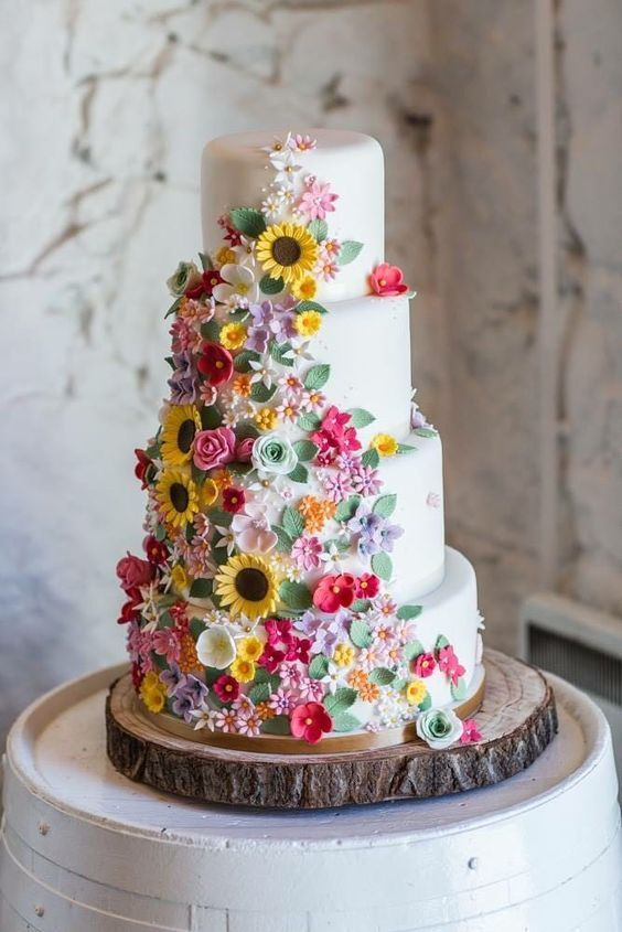a whimsical white four tier wedding cake with super bright sugar blooms and leaves is a stunning and bright idea