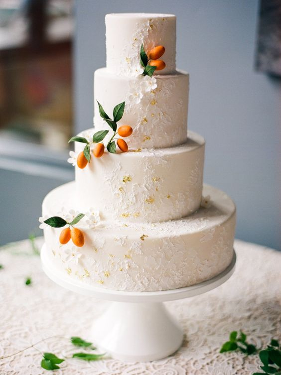 a white textural four tier wedding cake with gold leaf and kumquats is a very lovely and fresh idea for a spring or summer wedding