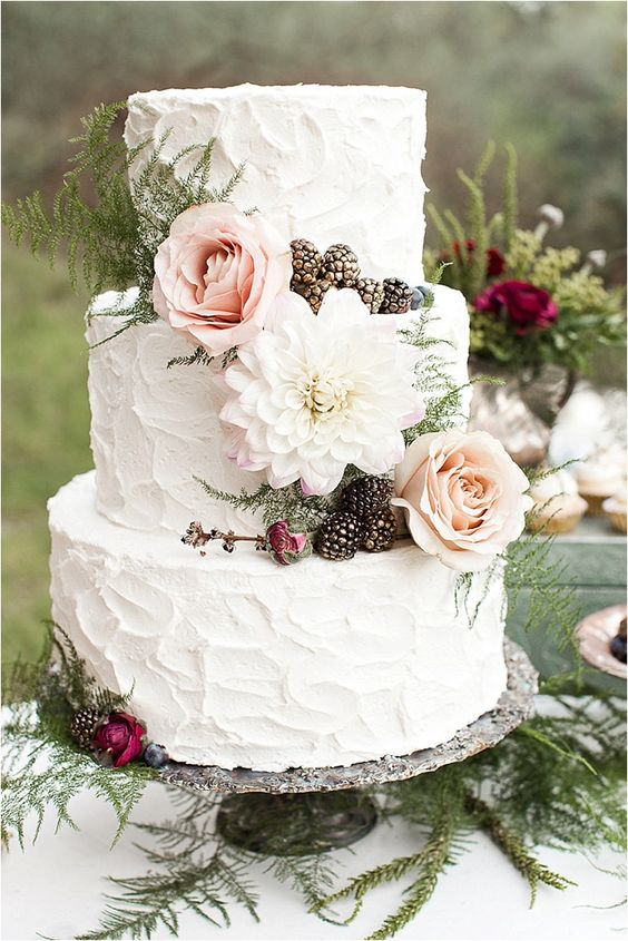 a white textural three-tier wedding cake with ferns, blackberries and pastel blooms is a fantastic and a bit rustic idea