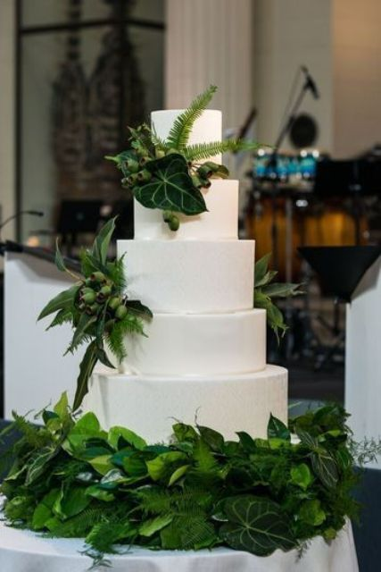 a white textural wedding cake decorated with leaves, ferns and berries is a bold idea for a woodland wedding