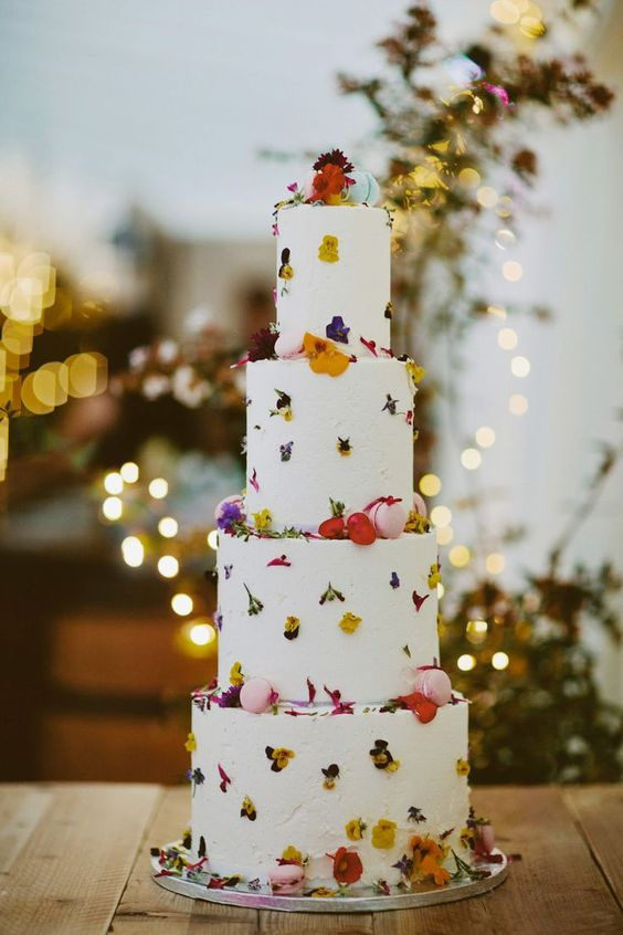 a white textural wedding cake with bright pressed blooms and pink macarons is a lovely idea for a spring or summer wedding