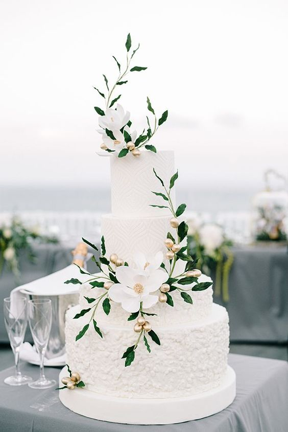 a white textural wedding cake with mismatching tiers, white blooms, gold olives and greenery is a very refined and cool idea