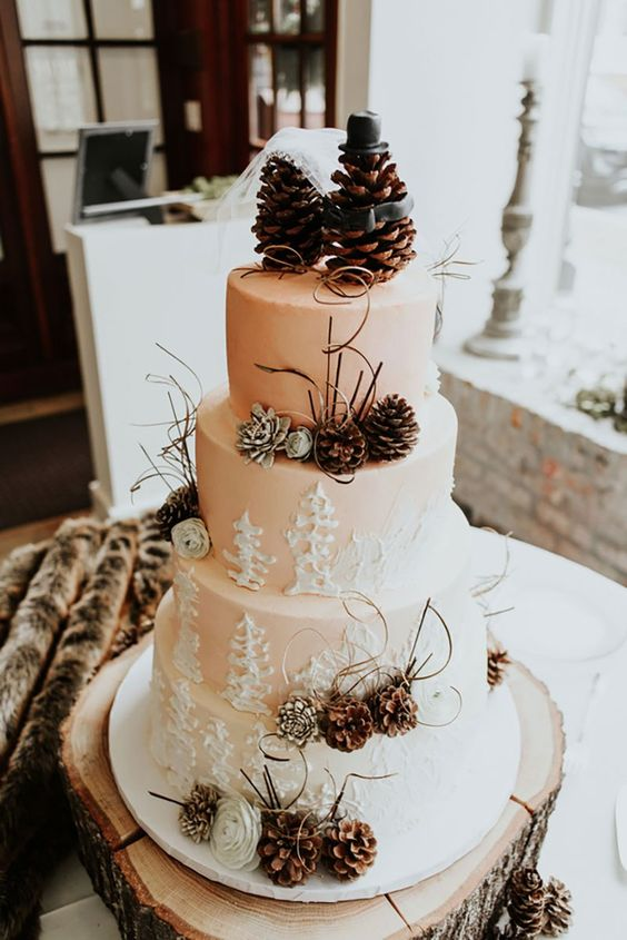 a winter blush four tier wedding cake with painted trees, pinecones, white blooms, twigs and funny pinecone toppers