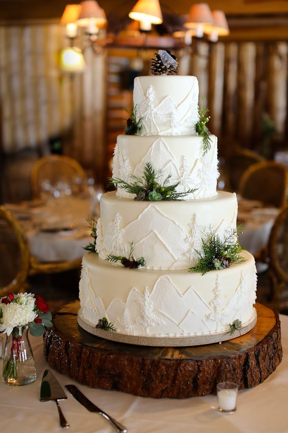 a winter mountain four tier wedding cake with painted mountains and trees, some greenery and pinecones and succulents is wow