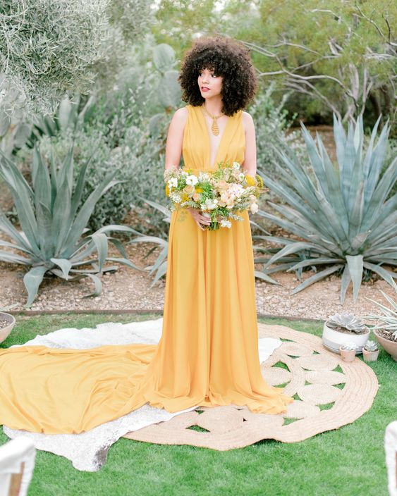a yellow A line wedding dress with a draped bodice and a plunging neckline, a skirt with a long train