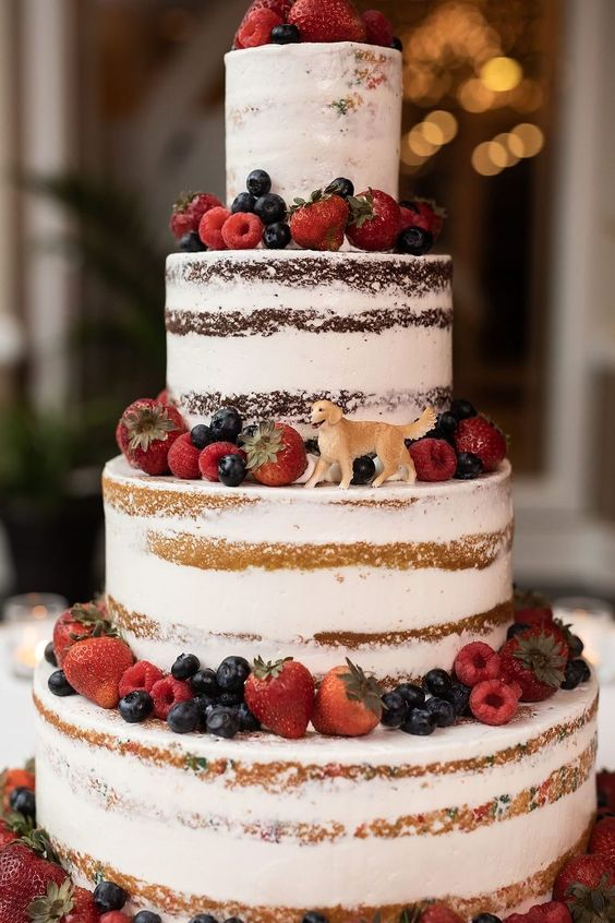 a yummy-looking naked four tier wedding cake topped with fresh berries and with a sugar dog topper is a fantastic idea