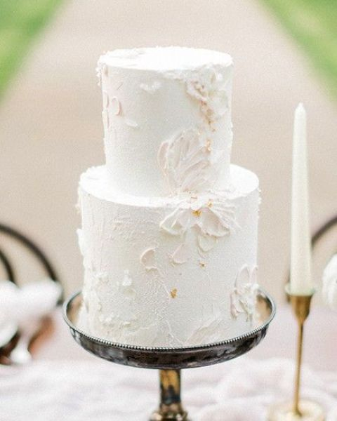 an airy neutral wedding cake with texture and floral patterns on it is a very refined and beautiful idea to rock