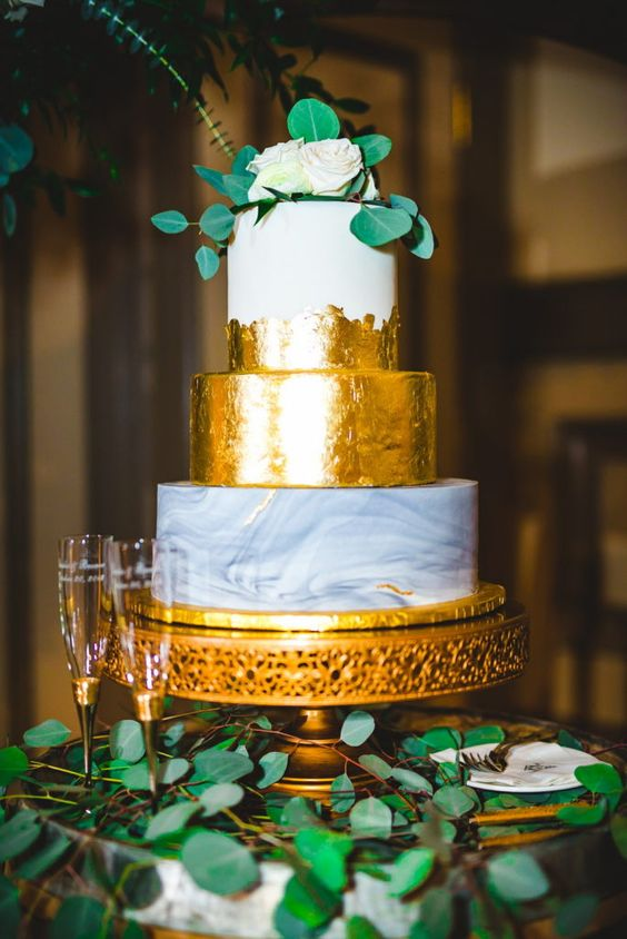 an elegant three-tier wedding cake with a grey marble, gold and partly gold tier, neutral blooms and greenery is amazing