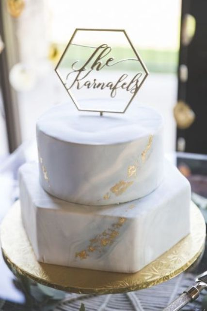 an elegant two-tier wedding cake with a round and a hexagon tier, gold and marble effect, a pretty cake topper