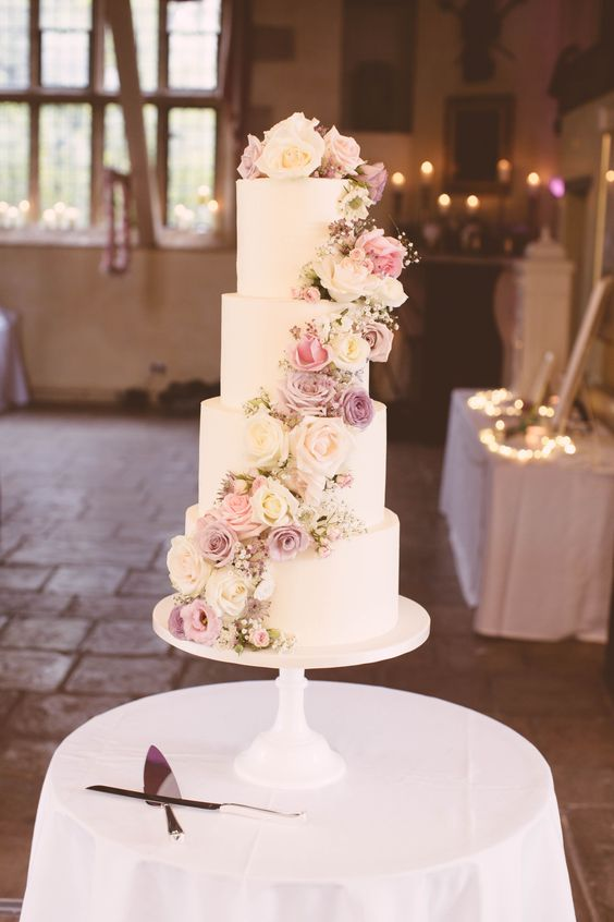 an elegant white plain four tier weddign cake decorated with pastel and neutral blooms, baby's breath is a gorgeous idea