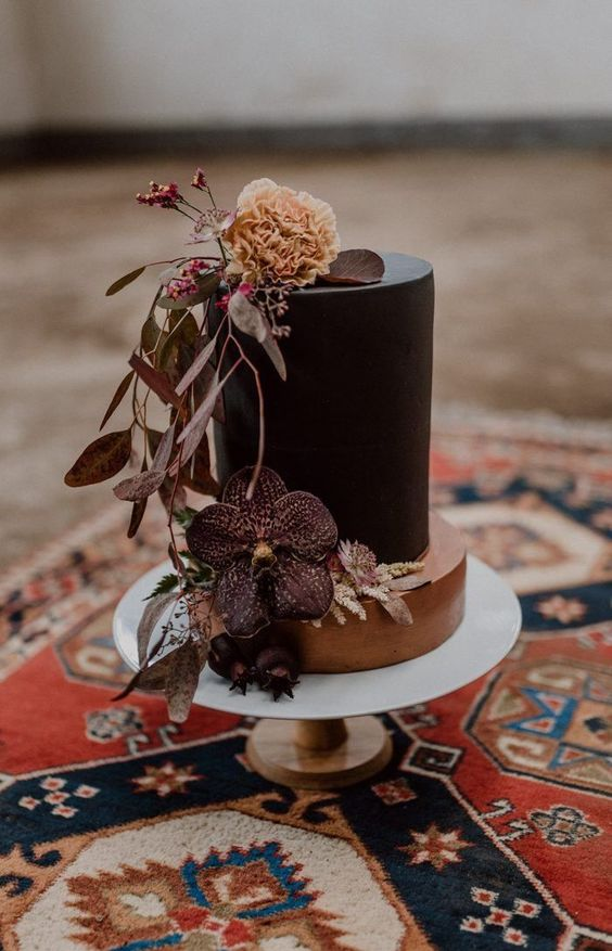 an unusual two-tier wedding cake with a copper and black tier, some moody blooms and foliage plus berries is lovely