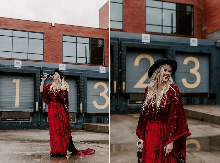 The bride was wearing a deep red lace boho wedding dress with a train, a black hat, a red lip and waves down