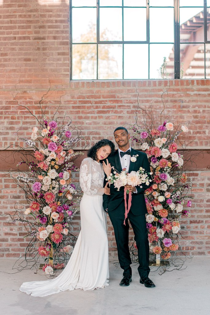 The groom was wearing a black tux and a white bloom boutonniere, and just look at the jaw-dropping wedidng altar of branches and bold blooms