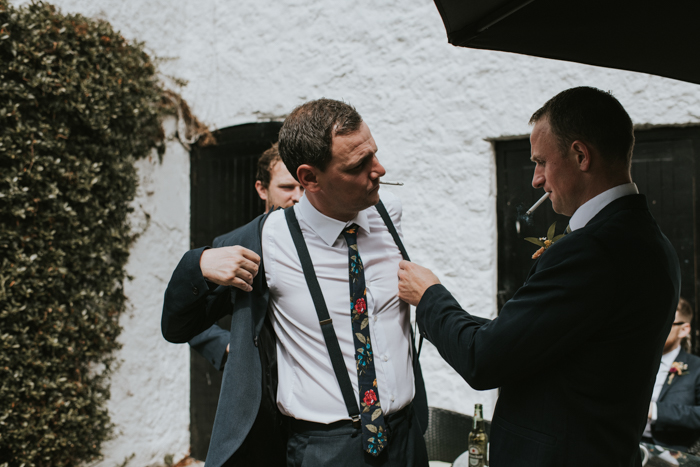 The groom was wearing a grey suit, suspenders and a colorful floral tie