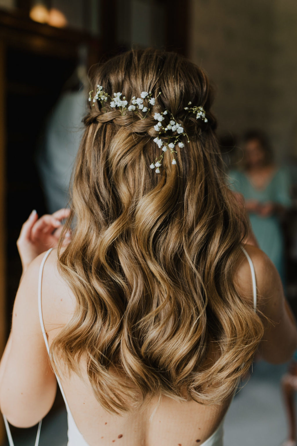The wedding hairstyle was done with waves and a braided halo, with baby's breath
