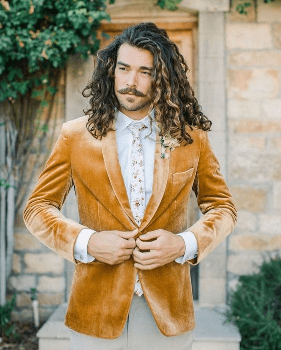 a boho look with a yellow velvet blazer, a white shirt, a floral tie and grey pants plus a floral boutonniere