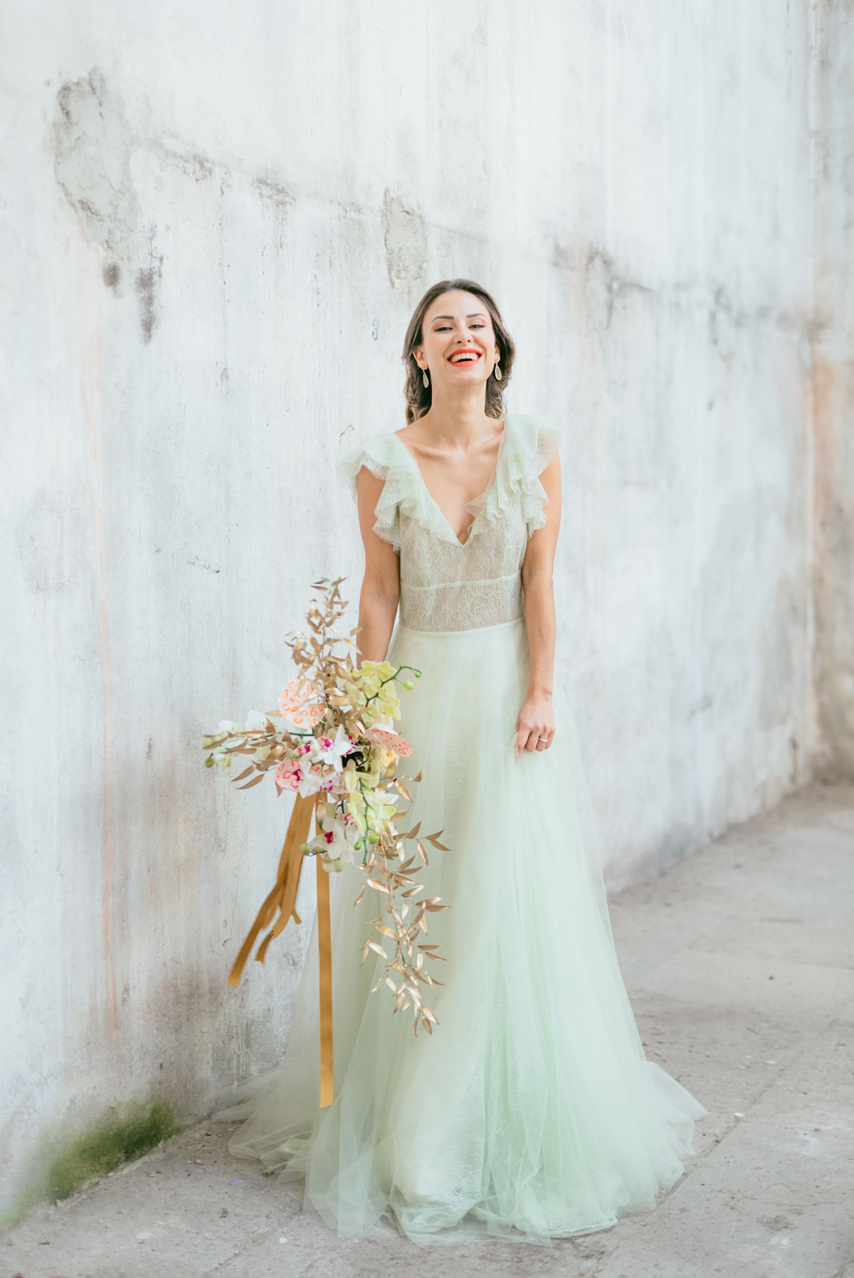 One bride was wearing a light mint A-line wedding dress with a ruffled neckline and a layered skirt