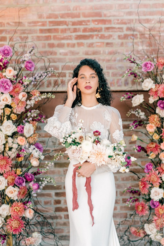 The bride was rocking a fantastic sheath wedding dress with floral appliques and a plain skirt plus statement earrings