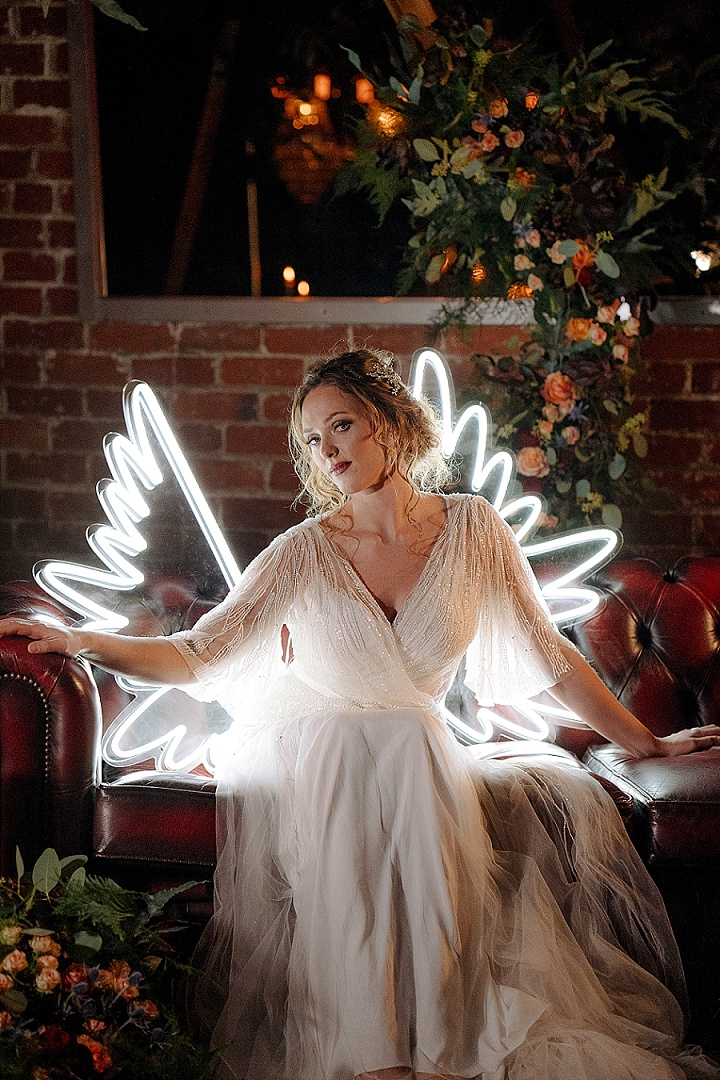 The bride was wearing an embellished wedding dress with a V-neckline and look at these neon wings