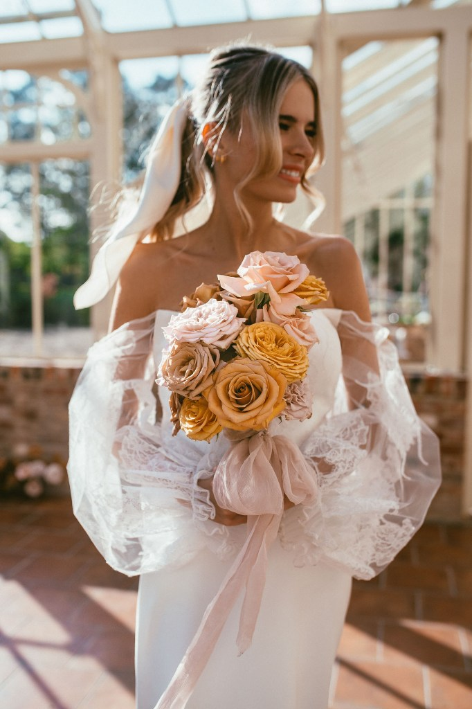 The wedding bouquet was done with blush and orange roses and a blush ribbon bow