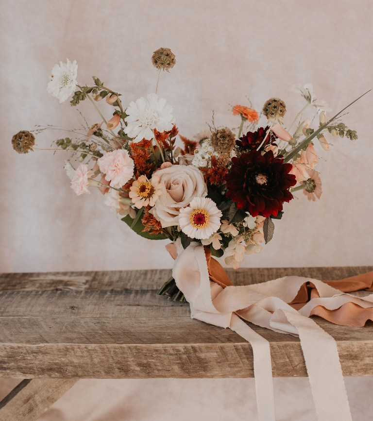 The wedding bouquet was done with blush and white blooms and burgundy accents