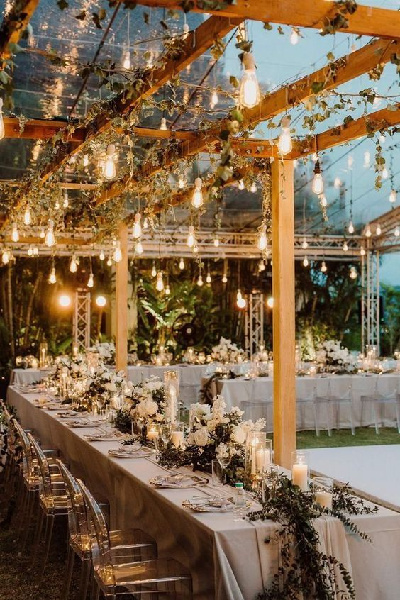 a beautiful wedding reception space outdoors, with a glass roof decorated with greenery and bulbs hanging down