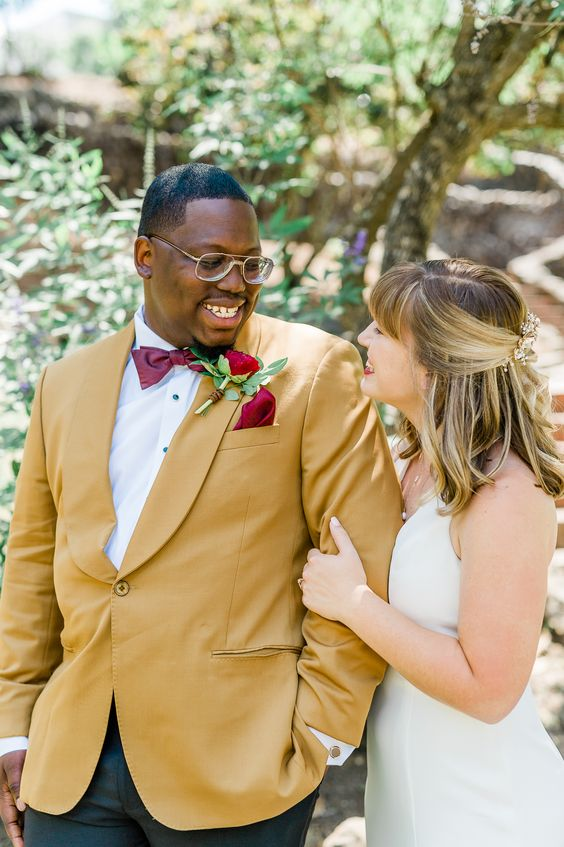 a bold groom's outfit with a mustard blazer, a white shirt, black pants, a burgundy bow tie and a deep red rose