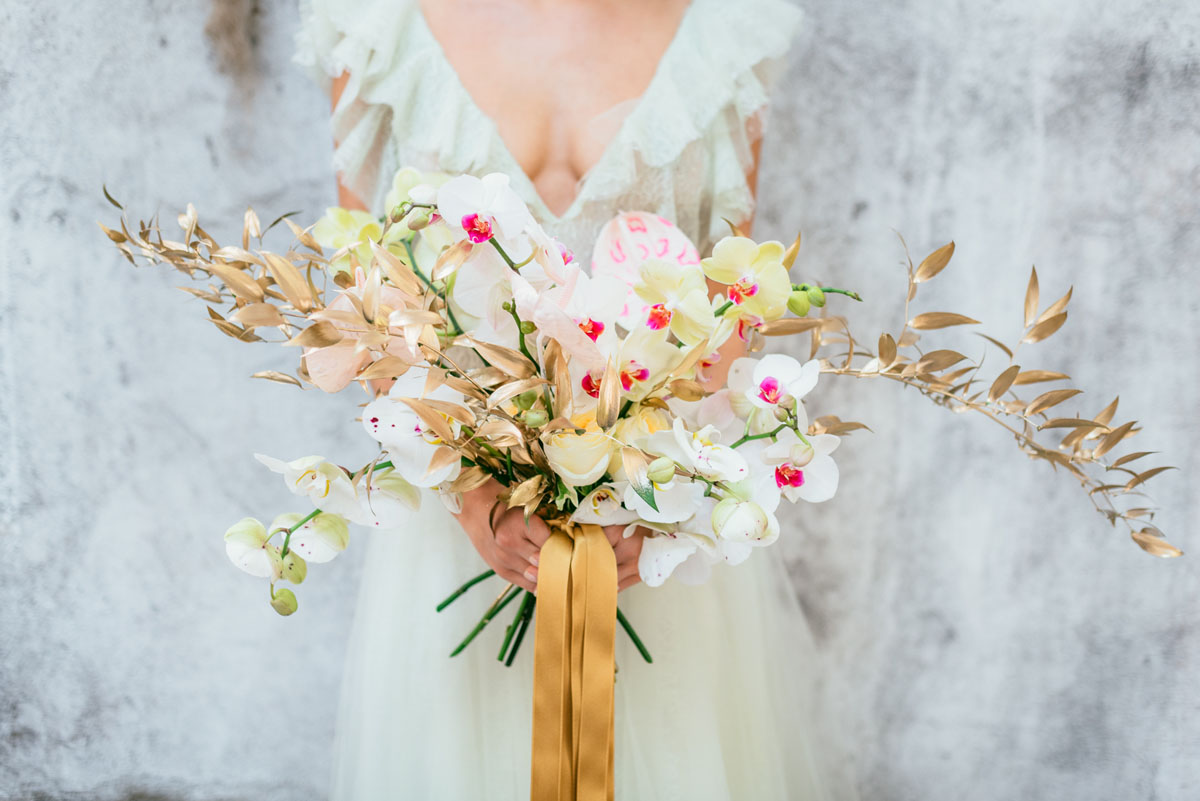 Her wedding bouquet was done with yellow blooms, gilded branches and orchids