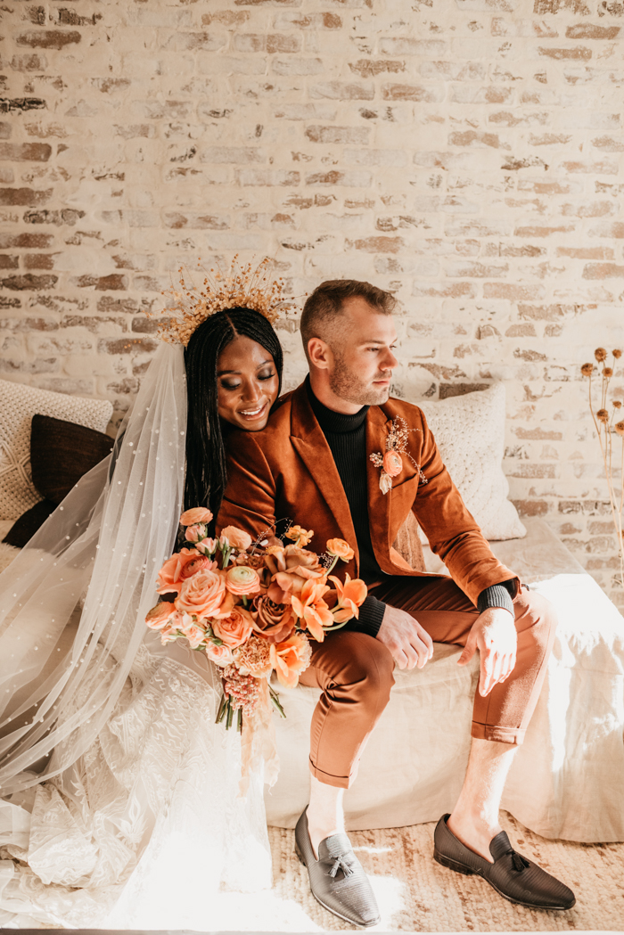 The groom was wearing a rust-colored suit, a black turtleneck, black loafers and a bold boutonniere
