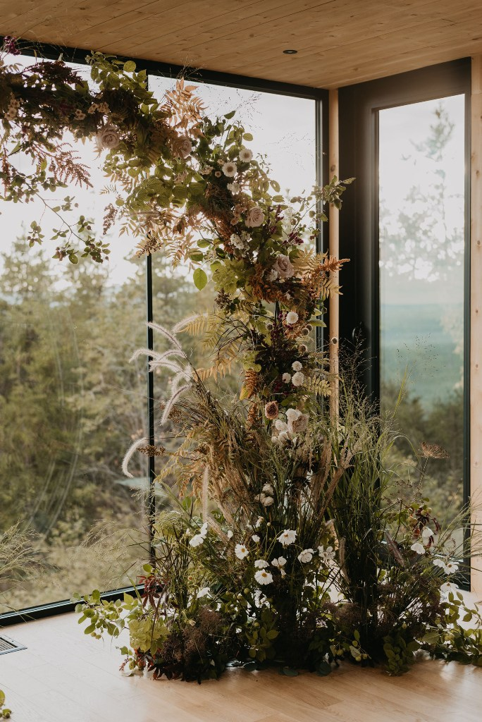 The wedding arch was jaw-dropping, with grasses and greenery of all kinds and just a bit of white blooms