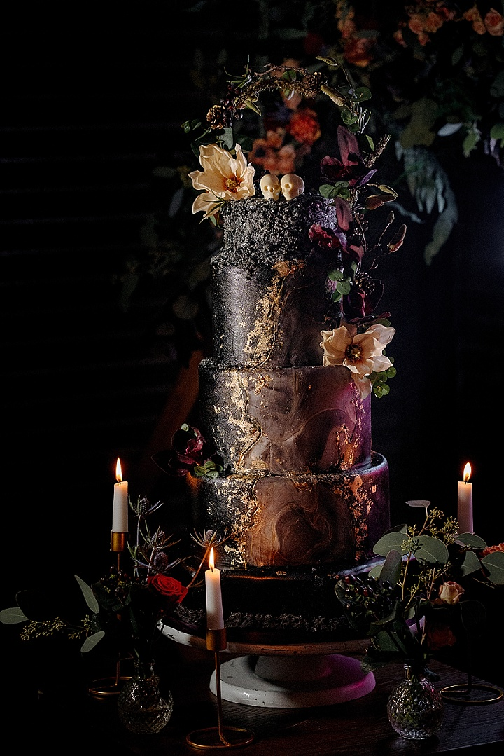 The wedding cake was a black marble one, with gold leaf and dark florals plus skulls on top