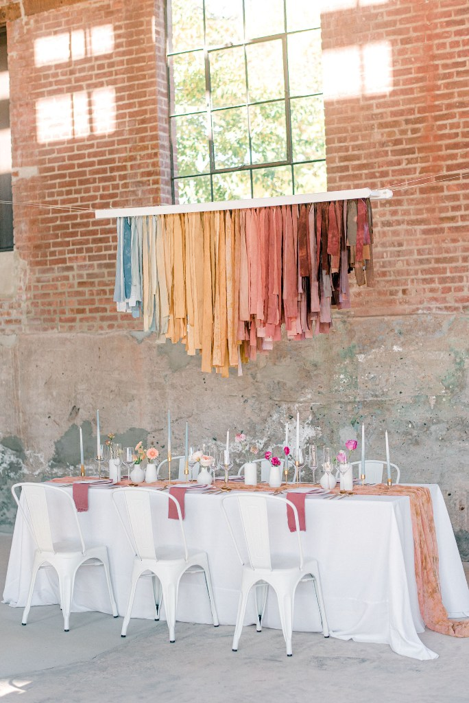 The wedding reception space was done with a rainbow fabric overhead installation